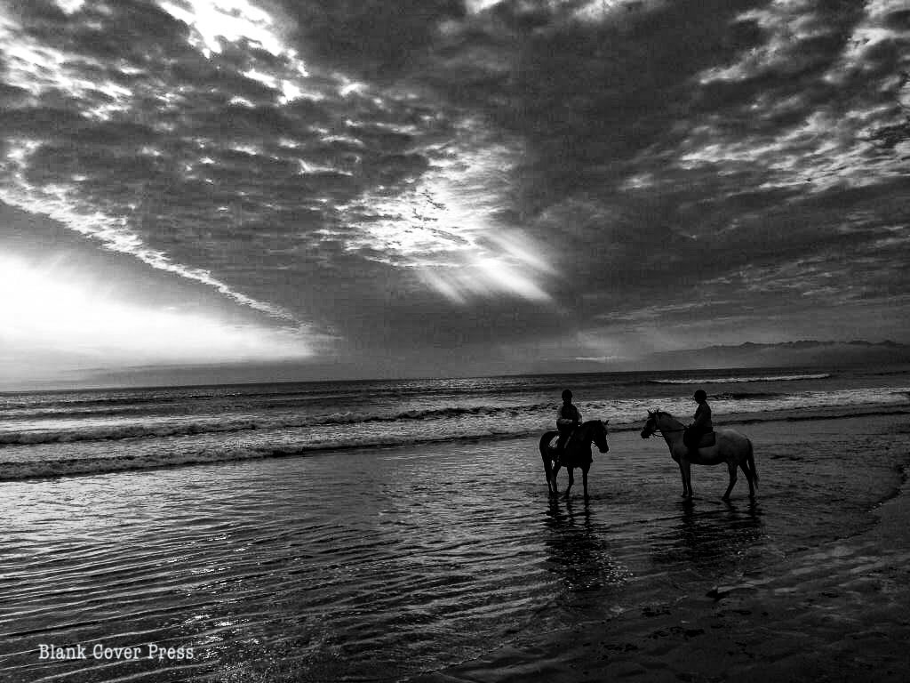 Silhouette of two people on horses on the beach
