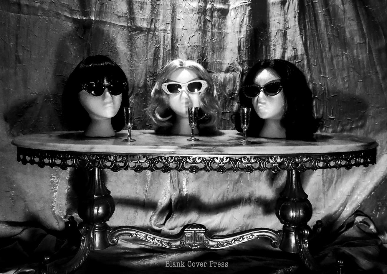 Three mannequin heads with wigs and sunglasses